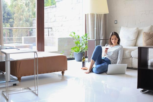 Mulher jovem sorridente, sentada no chão com o computador laptop e conversando com amigos, bebendo vinho.