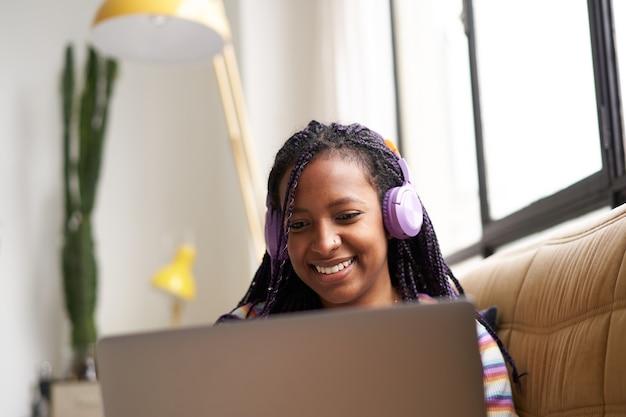 Mulher jovem sorridente, sentada no sofá com fones de ouvido, trabalhando em casa com um laptop