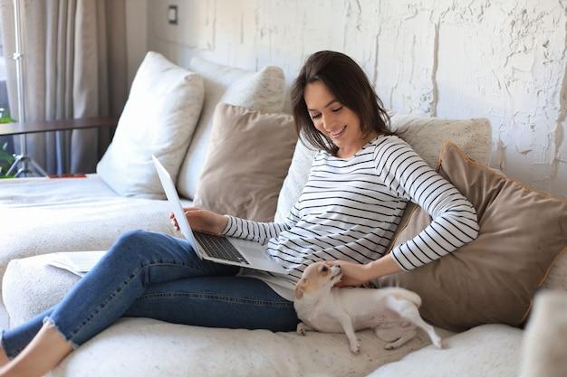 Mulher jovem sorridente, sentado no sofá com o computador portátil e conversando com amigos, cachorrinho brincando perto.