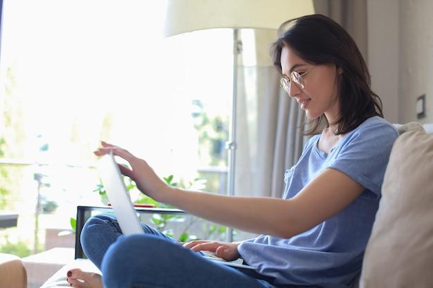 Mulher jovem sorridente, sentado no sofá com o computador portátil e conversando com amigos.
