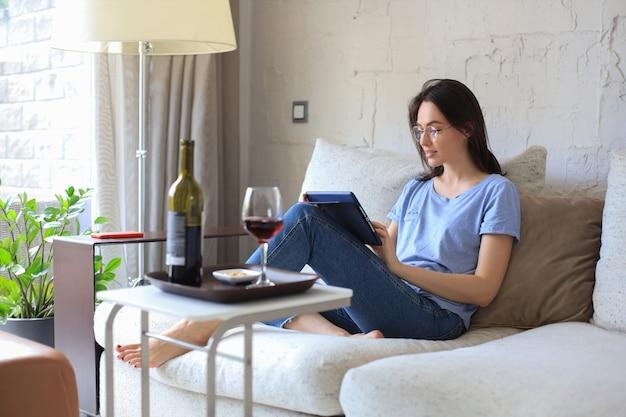 Mulher jovem sorridente, sentado no sofá com o tablet digital e conversando com amigos, bebendo vinho.