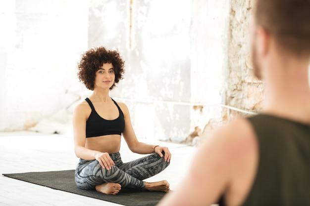 Mulher jovem sorridente, tendo uma aula de ioga com instrutor masculino