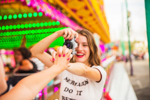 Mulher jovem sorridente tirando foto da câmera segurando a mão de sua amiga