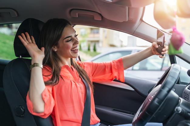Mulher jovem sorridente tirando foto de selfie com a câmera do telefone inteligente ao ar livre no carro.