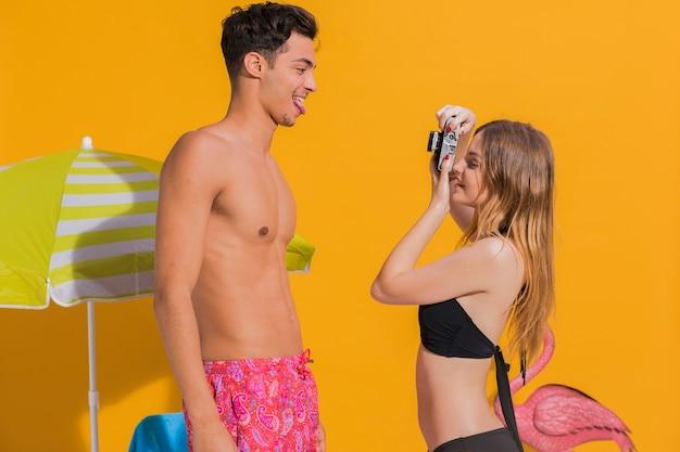 Mulher jovem sorridente tirando fotos de namorado em fundo amarelo
