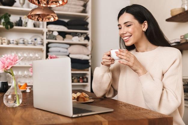 Mulher jovem sorridente tomando café da manhã enquanto está sentado na cozinha e usando um laptop