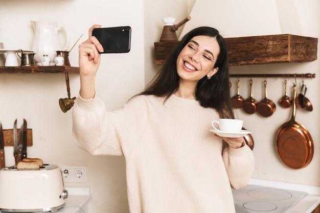Mulher jovem sorridente tomando uma xícara de café na cozinha, tirando uma selfie