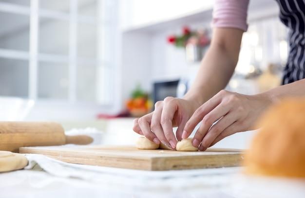 Mulher jovem sorridente trabalhando com pino de rolo de madeira fazendo torta doce ou massa folhada na cozinha, mulher feliz milenar amorosa cozinhando em avental preparando o jantar em família ou assando pães de sobremesa