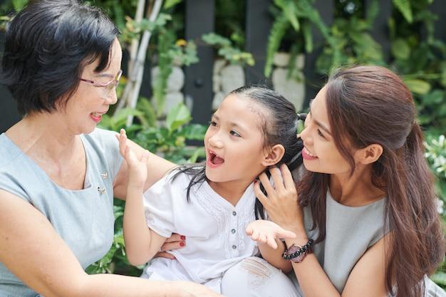 Mulher jovem sorridente trazendo a filha animada para a avó nos feriados