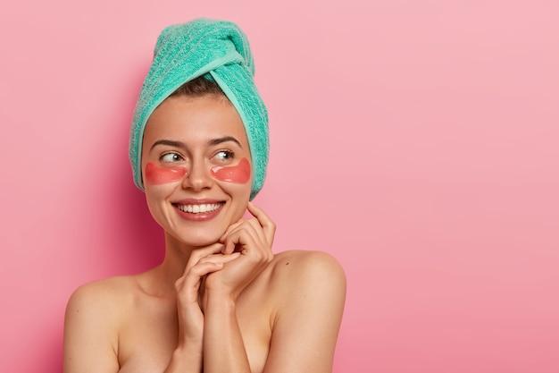Mulher jovem sorridente usa adesivos cosméticos hidratantes sob os olhos, remove rugas, se preocupa com a pele, usa toalha macia na cabeça, faz procedimentos cosméticos