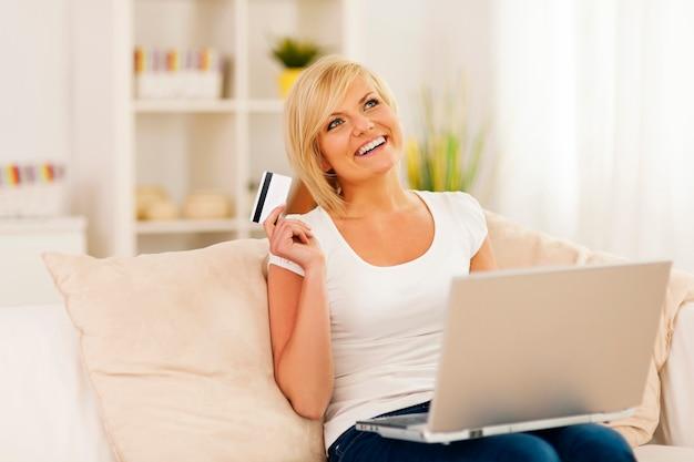 Mulher jovem sorridente usando laptop e segurando um cartão de crédito