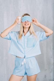 Mulher jovem sorridente usando máscara de olho azul dormindo contra a parede