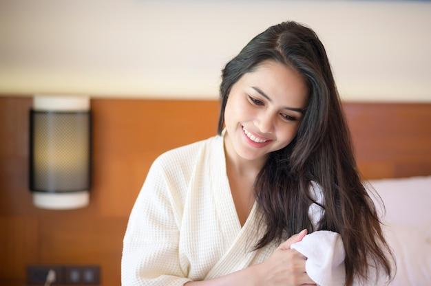 Mulher jovem sorridente usando roupão de banho branco, enxugando o cabelo com uma toalha depois do banho no quarto
