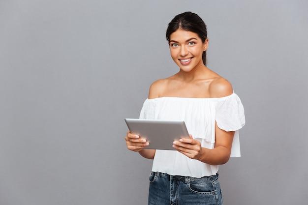 Mulher jovem sorridente usando um computador tablet e olhando para a frente, isolada em uma parede cinza
