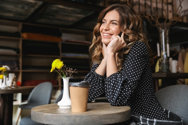 Mulher jovem sorridente usando um telefone celular enquanto está sentado no café tomando café