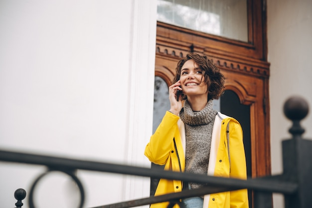 Mulher jovem sorridente, vestida com capa de chuva