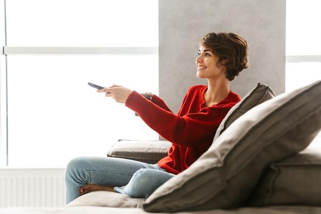 Mulher jovem sorridente, vestindo um suéter, relaxando no sofá em casa, bebendo café