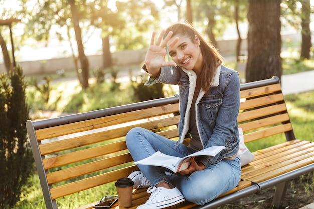 Mulher jovem sorridente, vestindo uma jaqueta, sentada em um banco do parque, lendo uma revista e acenando com a mão