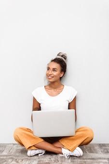Mulher jovem sorridente, vestindo uma roupa casual, sentada isolada no branco, segurando o laptop no colo, olhando para longe