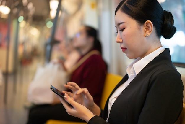 Mulher jovem sorridente, viajando de ônibus e usando telefone inteligente