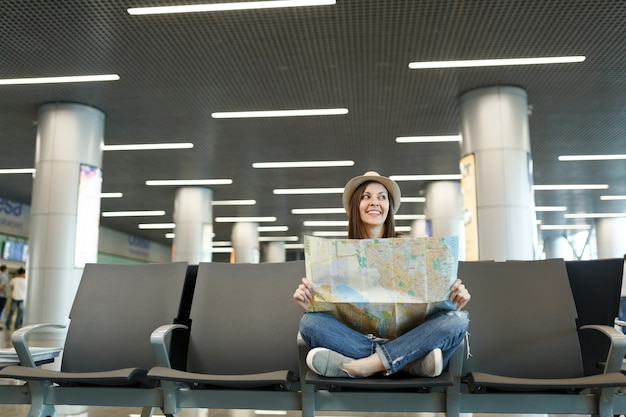 Mulher jovem sorridente viajante turista com as pernas cruzadas segurando um mapa de papel olhando de lado, esperando no saguão do aeroporto internacional