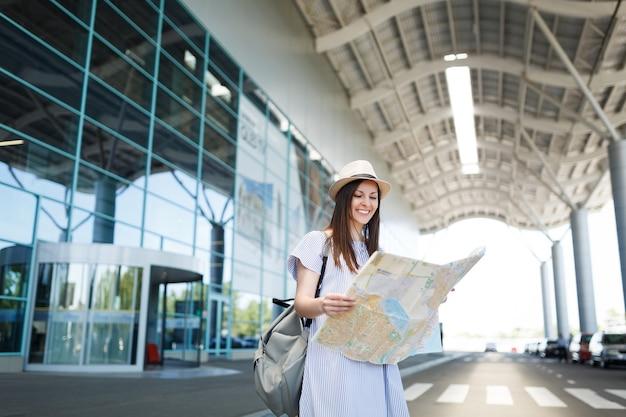 Mulher jovem sorridente viajante turista com mochila segurando um mapa de papel no aeroporto internacional