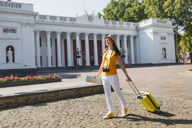 Mulher jovem sorridente viajante turista no chapéu de roupas casuais de verão amarelo com mapa da cidade mala andando na cidade ao ar livre. garota viajando para o exterior para viajar na escapadela de fins de semana. estilo de vida da viagem de turismo.