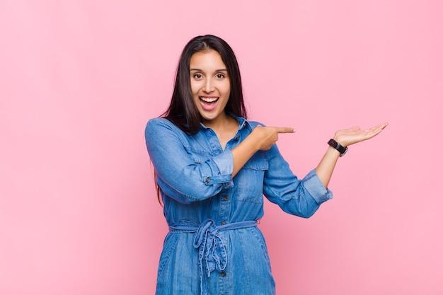 Mulher jovem sorrindo alegremente e apontando para copiar o espaço na palma da mão ao lado, mostrando ou anunciando um objeto