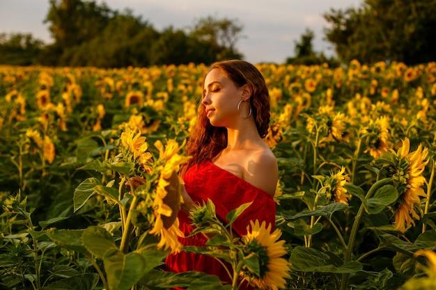 Mulher jovem sorrindo ao pôr do sol em um campo de girassóis
