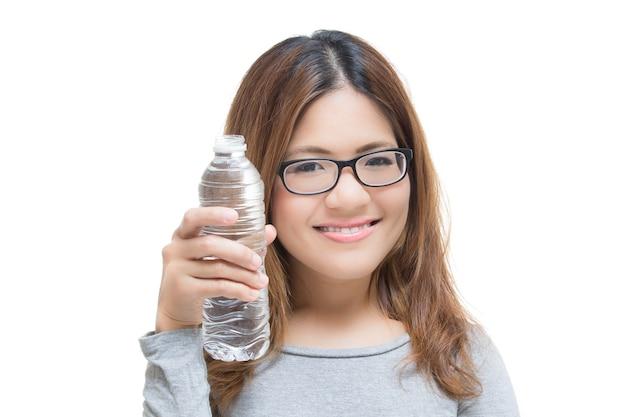 Mulher jovem sorrindo com a mão segurando uma garrafa de água