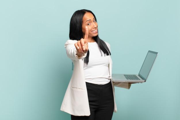 Mulher jovem sorrindo com orgulho e confiança fazendo a pose número um triunfantemente, sentindo-se uma líder