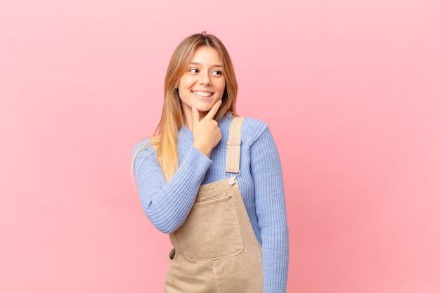 Mulher jovem sorrindo com uma expressão feliz e confiante com a mão no queixo Foto Premium
