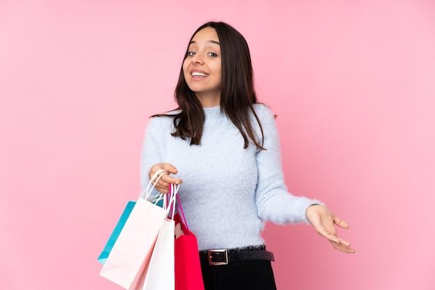 Mulher jovem sorrindo com uma sacola de compras sobre uma parede rosa isolada