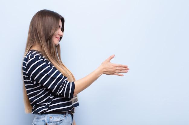 Mulher jovem sorrindo, cumprimentando você e oferecendo um aperto de mão para fechar um negócio de sucesso, o conceito de cooperação na parede azul suave