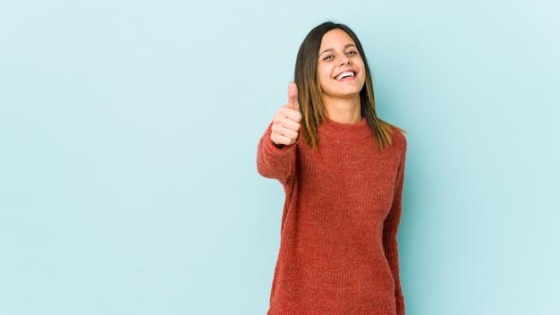 Mulher jovem sorrindo e levantando o polegar