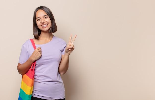 Mulher jovem sorrindo e parecendo amigável, mostrando o número dois ou o segundo com a mão para a frente, em contagem regressiva