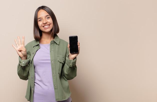 Mulher jovem sorrindo e parecendo amigável, mostrando o número quatro ou o quarto com a mão para a frente, em contagem regressiva