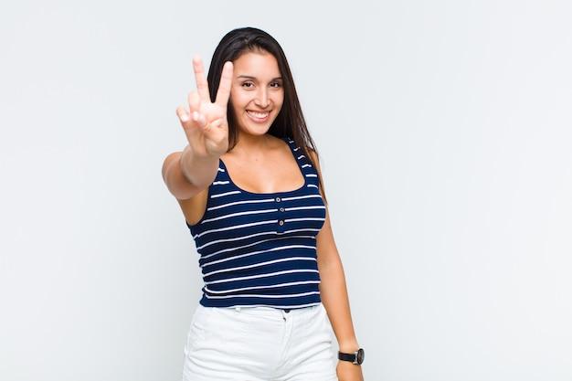 Mulher jovem sorrindo e parecendo feliz, despreocupada e positiva, gesticulando vitória ou paz com uma mão
