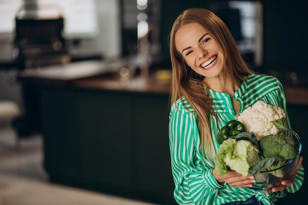 Mulher jovem sorrindo e segurando couve-flor
