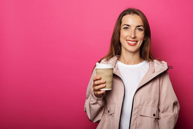 Mulher jovem sorrindo e segurando um copo de papel com café