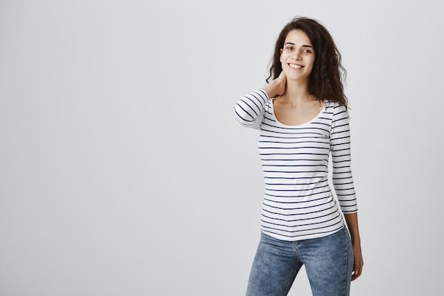 Mulher jovem sorrindo e tocando o pescoço modesto
