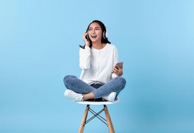 Mulher jovem sorrindo e usando fones de ouvido sem fio