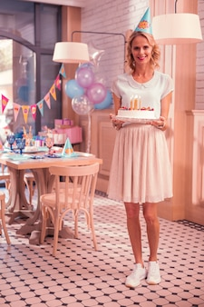 Mulher jovem sorrindo e usando um chapéu de festa segurando um bolo delicioso