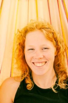 Mulher jovem, sorrindo, enquanto, olhando câmera