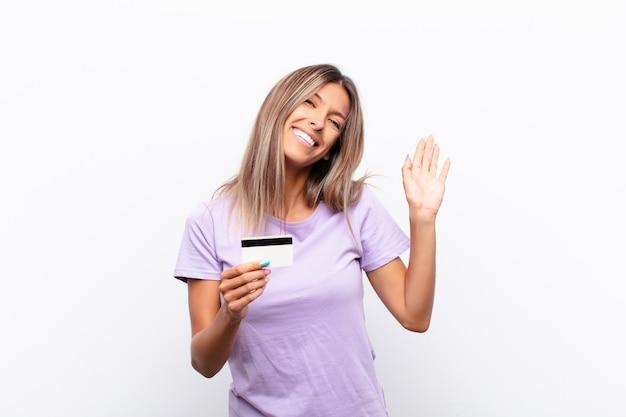 Mulher jovem sorrindo feliz e alegremente, acenando com a mão, dando as boas-vindas e cumprimentando você ou se despedindo com um cartão de crédito