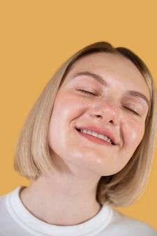 Mulher jovem sorrindo isolada em amarelo