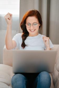 Mulher jovem sorrindo olha para a tela do laptop comemora a vitória e mostra um gesto de sim a co ...