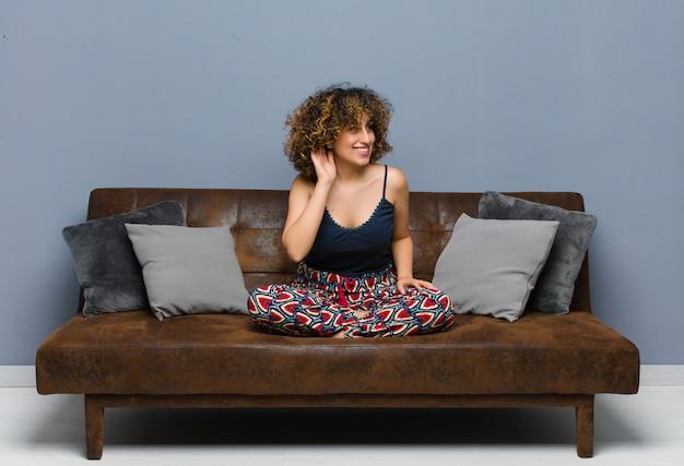 Mulher jovem sorrindo, olhando curiosamente para o lado, tentando ouvir uma fofoca ou ouvindo um segredo sentada em um sofá.