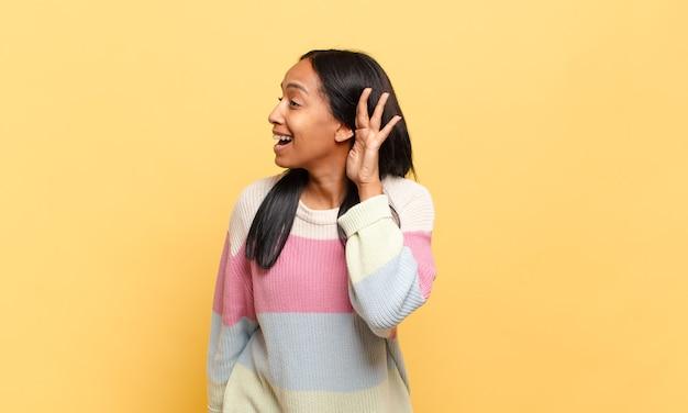 Mulher jovem sorrindo, olhando curiosamente para o lado, tentando ouvir uma fofoca ou ouvindo um segredo