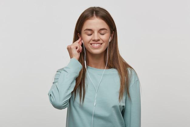 Mulher jovem, sorrindo, ouve música favorita com fones de ouvido, segurando o fone de ouvido com uma mão